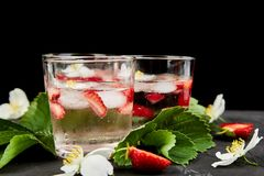 Strawberry detox water with jasmine flower. Summer iced drink or tea. Lemonade with berry. Flavored Water in glasses with Fresh Strawberry. Diet royalty free stock image