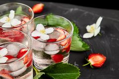 Strawberry detox water with jasmine flower. Summer iced drink or tea. Lemonade with berry. Flavored Water in glasses with Fresh Strawberry. Diet royalty free stock photo