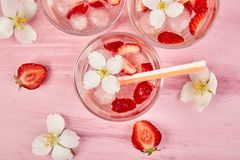 Strawberry detox water with jasmine flower. Summer iced drink. Or tea. Lemonade with berry. Flavored Water in glasses with Fresh Strawberry. Copy Space. Diet stock photo