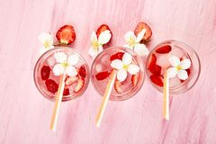 Strawberry detox water with jasmine flower. Summer iced drink or tea. Lemonade with berry. Flavored Water in glasses with Fresh Strawberry. Copy Space. Diet stock images