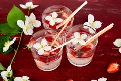 Strawberry detox water with jasmine flower. Summer iced drink. Or tea. Lemonade with berry. Flavored Water in glasses with Fresh Strawberry. Copy Space. Diet royalty free stock image