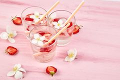 Strawberry detox water with jasmine flower. Summer iced drink or tea. Lemonade with berry. Flavored Water in glasses with Fresh Strawberry. Diet stock images