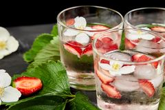 Strawberry detox water with jasmine flower. Summer iced drink or tea. Lemonade with berry. Flavored Water in glasses with Fresh Strawberry. Diet royalty free stock images