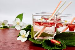 Strawberry detox water with jasmine flower. Summer iced drink or tea. Lemonade with berry. Flavored Water in glasses with Fresh Strawberry. Diet royalty free stock photography
