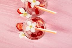 Strawberry detox water with jasmine flower. Summer iced drink or tea. Lemonade with berry. Flavored Water in glasses with Fresh Strawberry. Copy Space. Diet stock photography