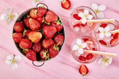 Strawberry detox water with jasmine flower. Summer iced drink or tea. Lemonade with berry. Flavored Water in glasses with Fresh Strawberry. Copy Space. Diet royalty free stock photography