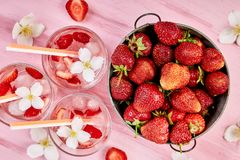 Strawberry detox water with jasmine flower. Summer iced drink or tea. Lemonade with berry. Flavored Water in glasses with Fresh Strawberry. Copy Space. Diet royalty free stock photo