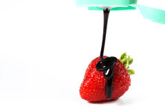 Strawberry dipped in chocolate fondue. Valentine's day on a white background Royalty Free Stock Photos