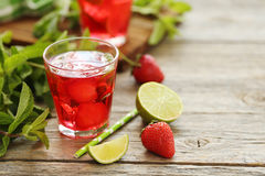 Strawberry drink. Fresh strawberry drink in glass with lime on wooden table Royalty Free Stock Photos