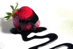 Strawberry drizzled with chocolate sauce. Ripe red strawberry drizzled with chocolate sauce leaving a zigzag trail on a white background Stock Images