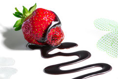 Strawberry drizzled with chocolate sauce. Ripe red strawberry drizzled with chocolate sauce leaving a zigzag trail on a white background Royalty Free Stock Photography