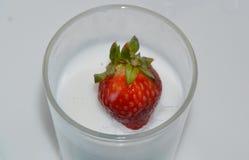 Strawberry drop on milk glass Royalty Free Stock Photo