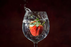 Strawberry drop on water, splashing out glass Royalty Free Stock Photos