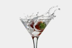 Strawberry dropped into a martini glass stock photos