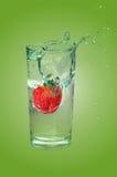Strawberry dropped in splashing water Stock Image