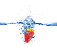 Strawberry dropped into water Stock Photos