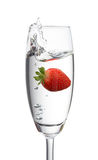 Strawberry dropping into a glass. Created splash Royalty Free Stock Photography