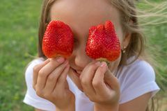 Strawberry Eyes . Beautiful young girl holding strawberries in eyes like binoculars in the garden. Healthy, lifestyle concept stock photography