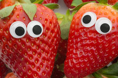 Strawberry face. Two strawberries with googly eyes on white background Stock Images