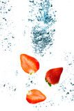 Strawberry are falling. In water with a big splash Stock Images