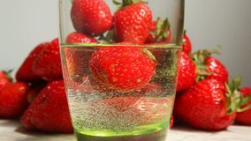 Strawberry falling into glass in water with splash, healthy food concept stock footage