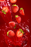 Strawberry falling into the lot of juice Royalty Free Stock Image