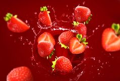 Strawberry falling into the lot of juice Royalty Free Stock Images