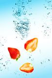 Strawberry are falling in water with a big splash. Abstract Stock Photo
