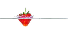 Strawberry falling into water with a splash Royalty Free Stock Photos