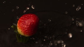 Strawberry falling on wet black surface stock video footage