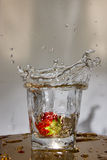 Strawberry falls with a splash in water. Royalty Free Stock Images