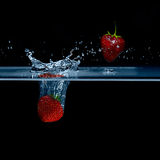 Strawberry falls into water. Strawberries in the air. Splash wat Stock Photo