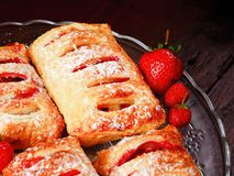 Strawberry filled puff pastry. Home made strawberry filled puff pastry on a glass platter. They are sprinkled with sugar Royalty Free Stock Photos
