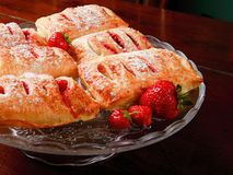 Strawberry filled puff pastry. Home made strawberry filled puff pastry on a glass platter. They are sprinkled with sugar Stock Image