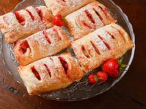 Strawberry filled puff pastry. Home made strawberry filled puff pastry on a glass platter. They are sprinkled with sugar Stock Photos