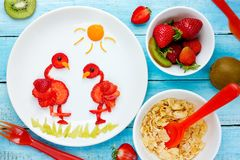 Strawberry food art for kids, edible flamingo. On plate from ripe fresh strawberries royalty free stock photos
