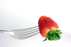 Strawberry on a fork. With a white background Stock Photography