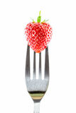 Strawberry on a fork against Royalty Free Stock Photos