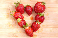 Strawberry in the form of heart on a chopping board Stock Image