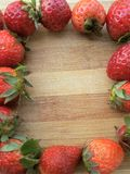 Strawberry frame on wooden background Royalty Free Stock Image