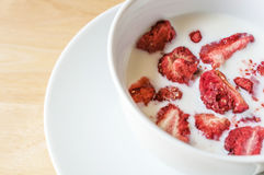 Strawberry freeze dry and milk. Strawberry freeze dry in milk cup on wooden table close up with copyspace Stock Images