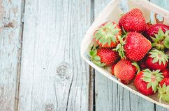 Strawberry. Fresh berries of strawberry on wooden table closeup/ Strawberry in small basket on natural wooden background. Top view. Strawberry. Fresh berries of stock photo