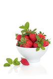 Strawberry Fruit and Mint Herb. Strawberry fruit with mint herb leaf sprigs in a porcelain bowl and scattered isolated over white background stock photos