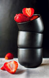 Strawberry geometry. Strawberries in black ceramic cups, placed one by one Stock Images