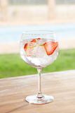 Strawberry gin and tonic cocktail by a pool outdoors Royalty Free Stock Images