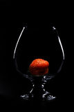 Strawberry in a glass. On a black background Royalty Free Stock Images