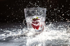 Strawberry in a glass of water with a splash. Photo of Strawberry in a glass of water with a splash Royalty Free Stock Photography