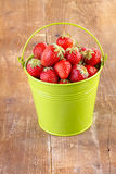 Strawberry in a green metal bucket on wood Royalty Free Stock Photos