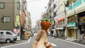 Strawberry hand holding with shops and street background. Strawberry by a hand holding with shops and street in the background Stock Photo