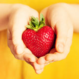 Strawberry in Hand. Red Berry Heart on Yellow Background Royalty Free Stock Image